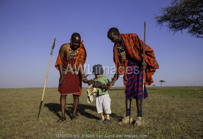 Kenya, Mara North Conservancy. Two Maasai play with a young guest.