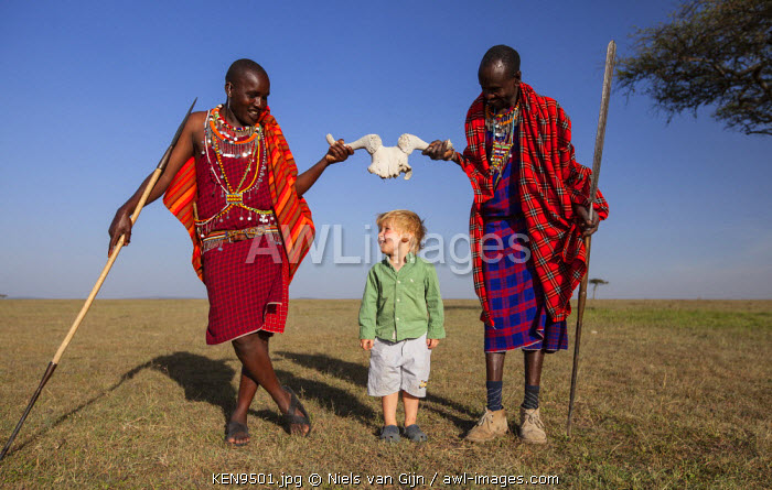 Kenya, Mara North Conservancy. Two Maasai play with a young guest.