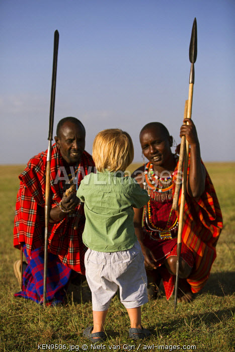 Kenya, Mara North Conservancy. A young guest explains something to two Maasai warriors.