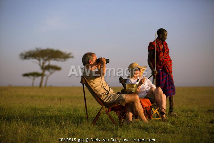 Kenya, Mara North Conservancy. A couple enjoy a sundowner on the plains of the Mara North Conservancy. MR.