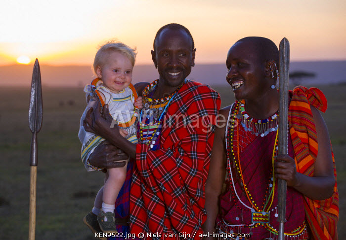 Kenya, Mara North Conservancy. Maasai warriors share a joke with very young guest.