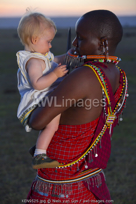 Kenya, Mara North Conservancy. A young girl plays with the jewellery of a Maasai.