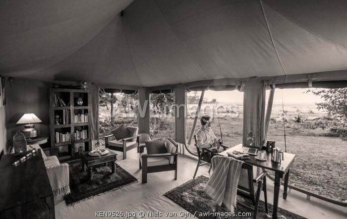 Kenya, Mara North Conservancy. A guest sits down to some work in the library of a luxury safari camp. MR.