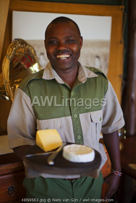 Kenya, Mara North Conservancy. A waiter serves the cheese board after lunch. MR.