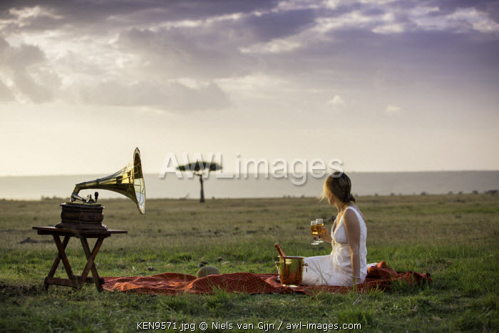 Kenya, Mara North Conservancy. A bride listens to music on a picnic rug in the Mara North Conservancy. MR.