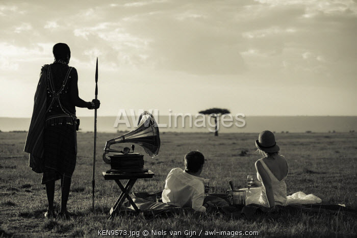 Kenya, Mara North Conservancy. A newly-wed couple toast with Champagne in the Mara. MR.