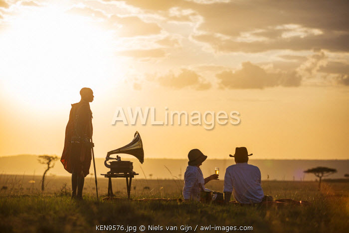 awl-images.com - Kenya / Kenya, Mara North Conservancy. A couple enjoy a sundowner in the Mara, listening to music from a vintage Gramophone. MR.