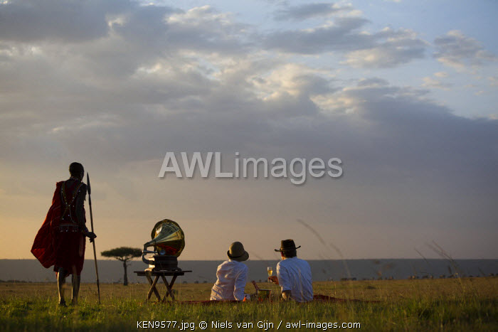 Kenya, Mara North Conservancy. A couple enjoy a sundowner in the Mara, listening to music from a vintage Gramophone. MR.