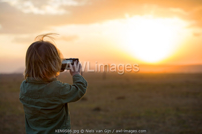 Kenya, Mara North Conservancy. A young boy takes a photo of the setting sun. MR.