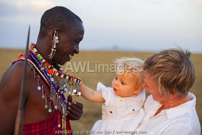 Kenya, Mara North Conservancy. A very young guest admires the colourful jewellery of a Maasai warrior. MR.