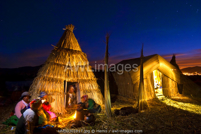 Peru, Puno Province, Titicaca lake, floating islands of Uros, evening family meal at home heated with dried reed