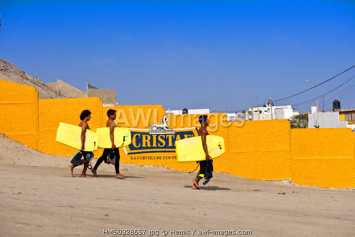 Peru, Lima Province, Puntas Rocas, bodyboarders going to the beach and passing in front of a Peruvian beer advert