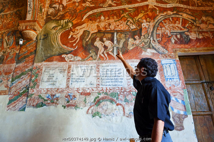 Peru, Cuzco Province,Andahuaylillas, Jesuit Father Luis Herrera facing a Baroque fresco depicting the Hell painted by Indian painters of Cuzco School, of the end of the 17th century