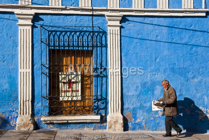 Peru, Arequipa Province, Arequipa, historical center listed as World Heritage by UNESCO, man reading a newspaper in front of a colourful facade