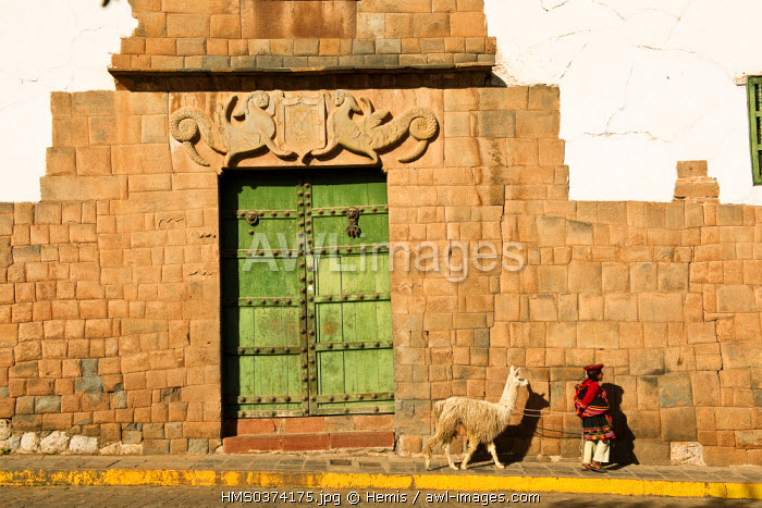 Peru, Cuzco Province, Cuzco, listed as World Heritage by UNESCO, Plaza de las Nazaneras, young Peruvian girl and her alpaca passing in front of Palacio Nazarenas decorated with Inca symbols