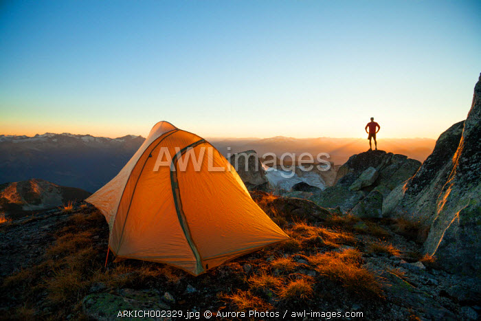 awl-images.com - Canada / A silhouetted hiker stands on a rock bluff while camping on the summit of Saxifrage Peak, Pemberton, BC, Canada.