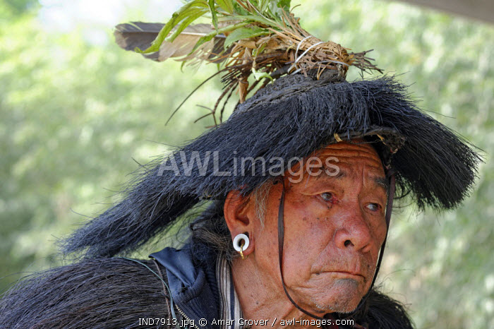 India, Arunachal Pradesh, Ziro Valley, near New Ziro. At Lempia a villager belonging to the Apatani tribe participates in traditional shamanic rituals. He wears a rudimentary rain hat surmounted with a feathered top-knot.