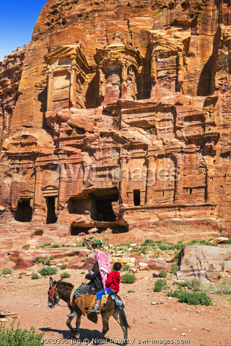 Jordan, Petra.  A Jordanian man and his son ride a donkey past the weathered Corinthian Tomb at Petra which is exquisitely carved into a hillside of pink sandstone.