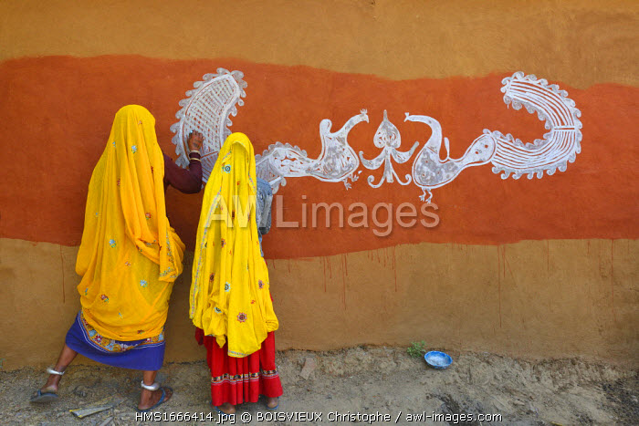 India, Rajasthan, Tonk region, Women painting clay walls prior to Diwali festival. These paintings are meant to welcome goddess Lakshmi and ward off evil spirits