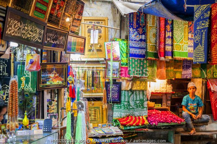 India, New Delhi, Nizamuddin West Muslim district, young salesman objects of worship next to the mausoleum of Sufi saint Nizamuddin Auliya of India