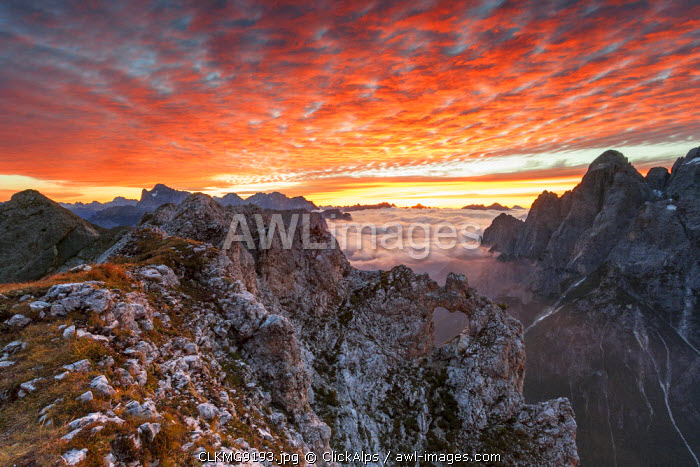 Colorful sunrise over the ridges of the Pale of the Balconies, Pala group, Dolomites, Italy. In the background mount Civetta, mount Moiazza and the sharp edges of Agner. Europe, Italy, Veneto, Agordino, Dolomites