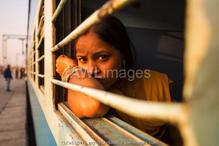 New Delhi, India. An Indian girl looking out the window of the train.