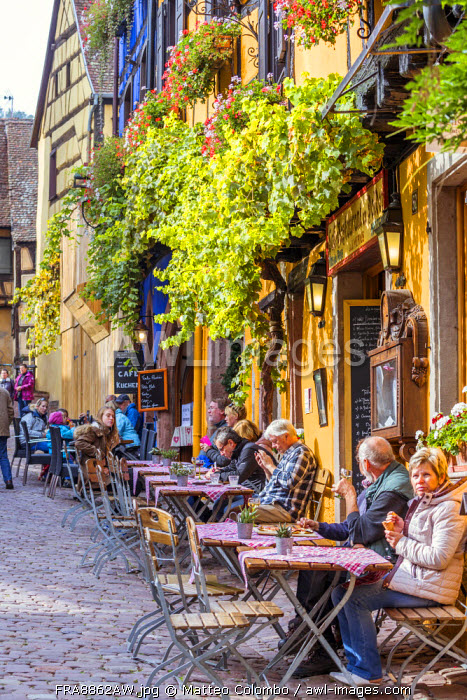 People sitting at coffee tables in the streets of Riquewihr, Alsace, France