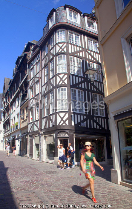 France, Normandy, Rouen. Young Woman walking through the streest in the historic centre. MR.