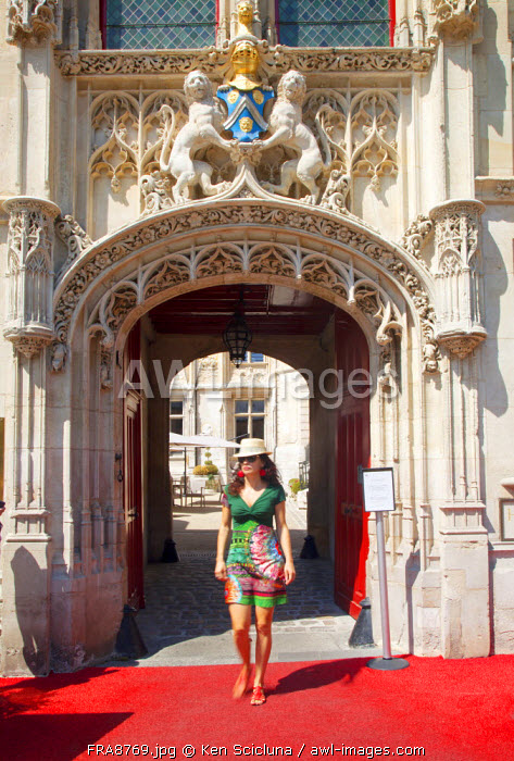 France, Normandy, Rouen. Woman walking under the entrance gate to a high end hotel in the historic centre. MR.