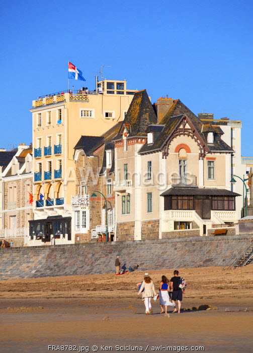 France, Brittany, Saint Malo. People walking along the shore with the flag of the town on one of the buildings.