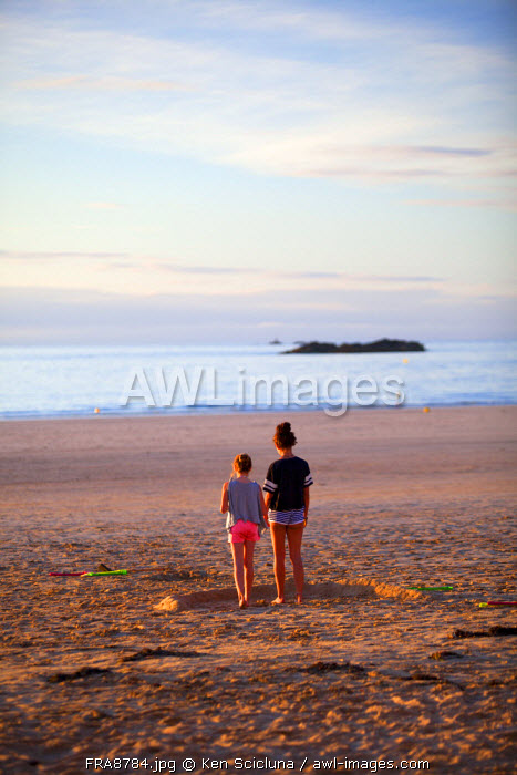 France, Brittany, Saint Malo. Two girls on the shore looking at the sea.