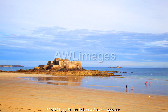 France, Brittany, Saint Malo. People walking along the shore with the Fortress in the background.