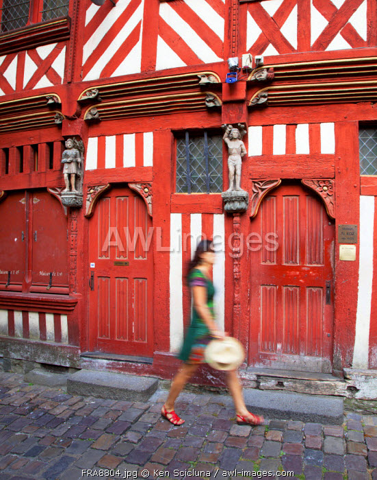 France, Brittany, Rennes. Young woman walking in front of a typical wooden coloured house in the historical centre. MR