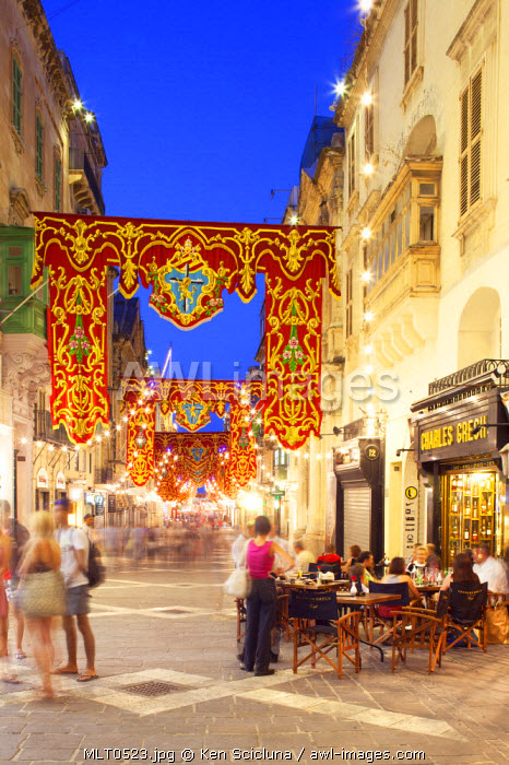 Europe, Maltese Islands, Malta. A cafe on Republic Street the main street in the capital of Valletta with feast decorations.