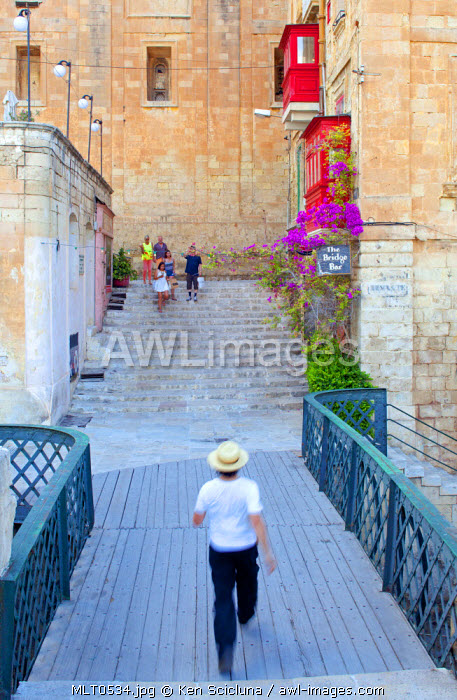 Europe, Maltese Islands, Malta. Man crossing a bridge built during the British rule with typical coloured balconies found on the islands.