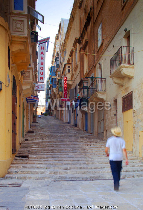 Europe, Maltese Islands, Malta. Man walking one of the famed streets of Valletta with a fusion of British influence and Baroque architecture dating back to the Knight of St.John.