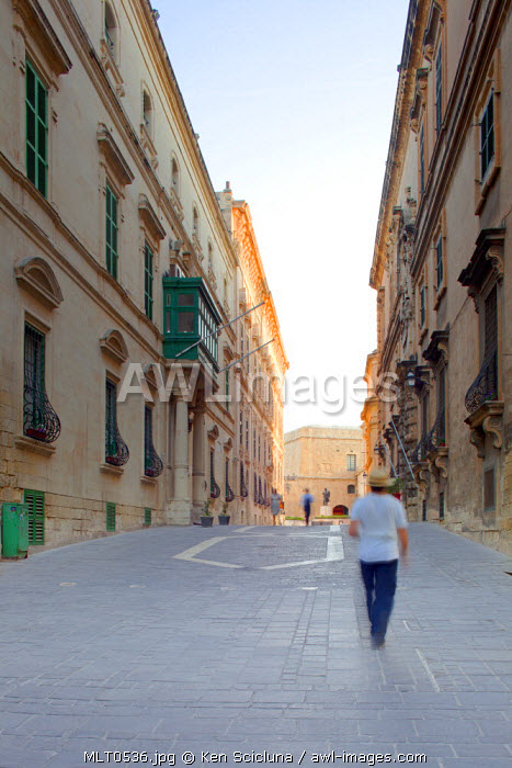 Europe, Maltese Islands, Malta. Man walking through the streets of Valletta in front of the Auberge d'Italie