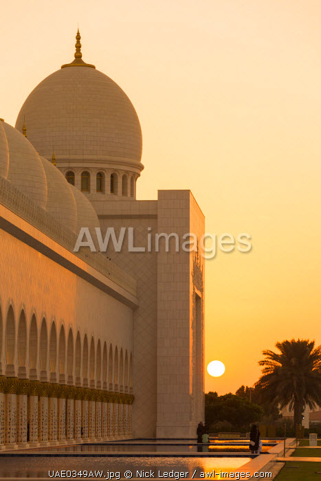 United Arab Emirates, Abu Dhabi. The white marble exterior and water pools of Sheikh Zayed Grand Mosque at sunset.