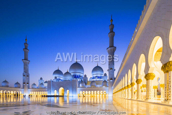 United Arab Emirates, Abu Dhabi. The courtyard and white marble exterior of Sheikh Zayed Grand Mosque. The spectacular evening lighting varies from white to blue according to the phases of the moon.