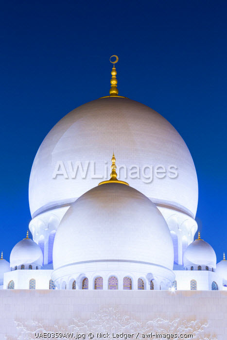 United Arab Emirates, Abu Dhabi. The white marble domes of Sheikh Zayed Grand Mosque. The main dome pictured is 85m high and comparable in size to St Paul's Cathedral. The spectacular evening lighting varies from white to blue according to the phases of the moon.
