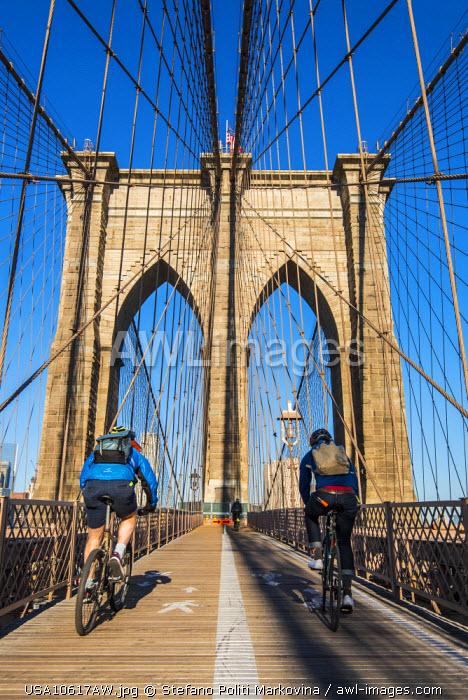Cyclists riding their bikes on Brooklyn Bridge, New York, USA