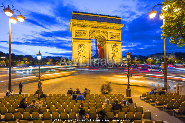 Arc de Triomphe with the French tricolour flag, illuminated at dusk, Paris, France