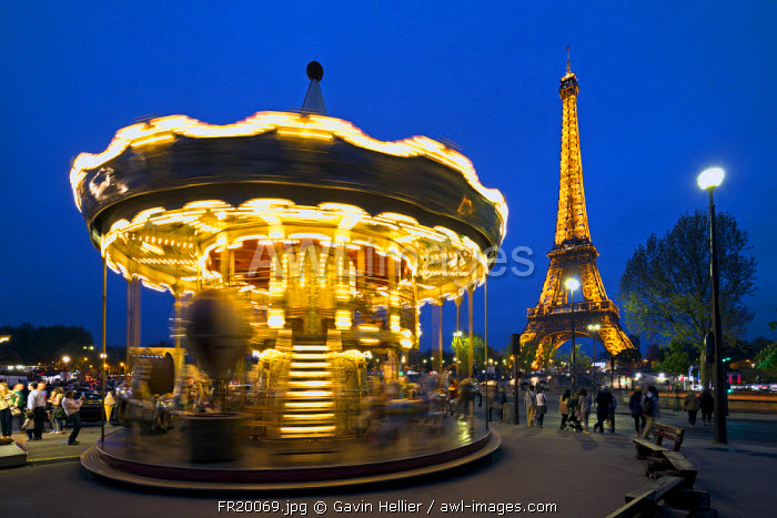 Carousel below the Eiffel Tower at twilight, Paris France