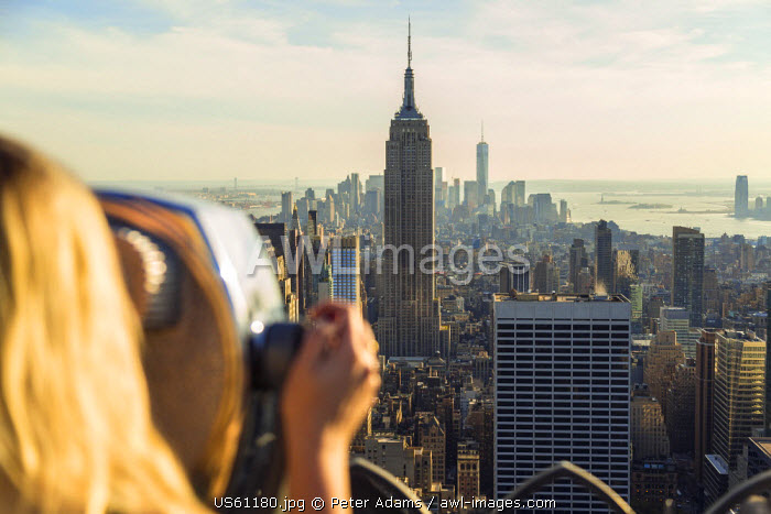 Woman looking through coin operated telescope over Empire State Building & Manhattan, New York, USA