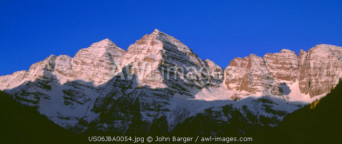 USA, Colorado, White River National Forest, Maroon Bells Snowmass Wilderness, Sunrise brightens the Maroon Bells which are whitened by autumn snow
