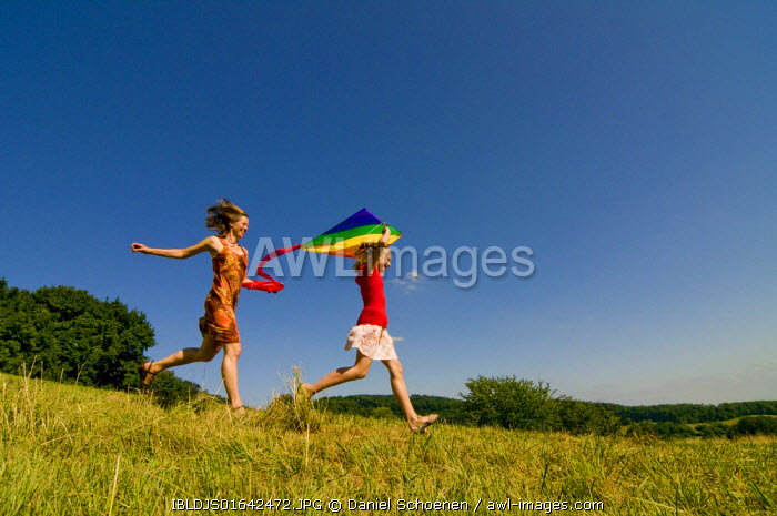 Woman and girl running with a kite in a meadow in the Black Forest, Baden-Wuerttemburg, Germany