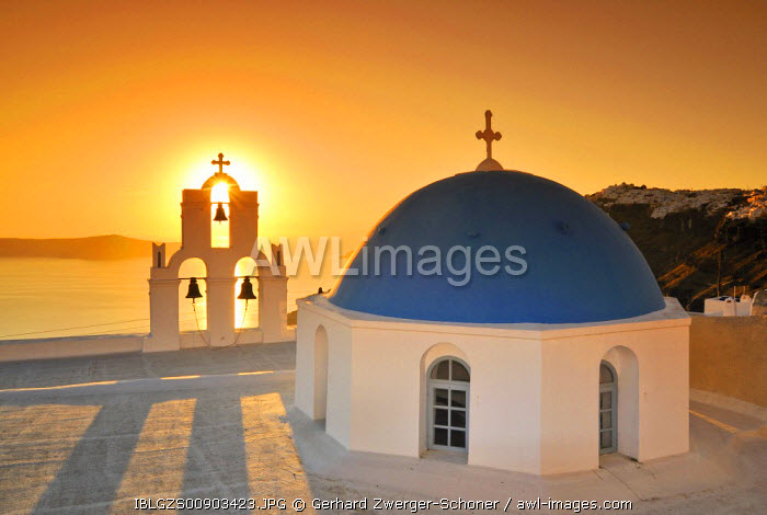 White Greek church with a blue dome and a bell tower at sunset, Firostefani, Santorini, Cyclades, Greece