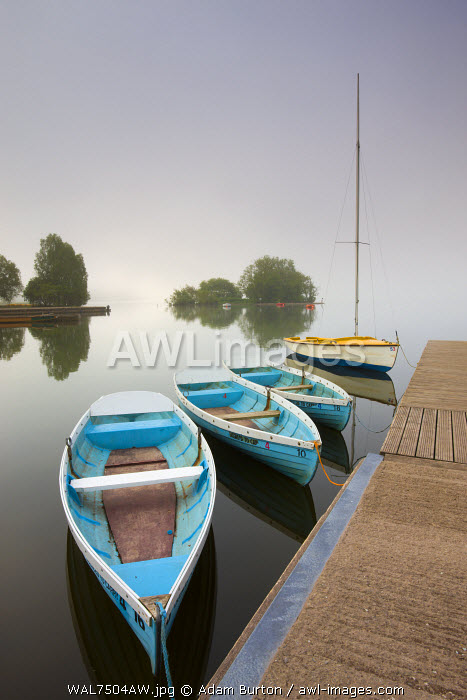 Pleasure boats moored at Llangorse Lake on a misty morning, Brecon Beacons National Park, Powys, Wales. Summer (June) 2009