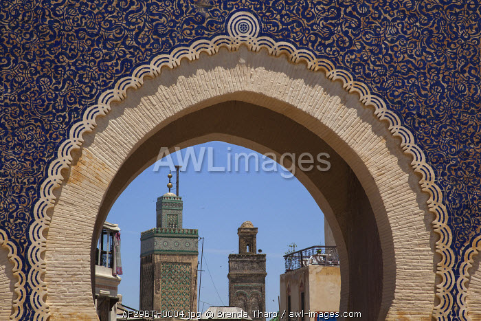 Africa, Morocco, Fes. An arch with classic Moorish decor frames two minarets.