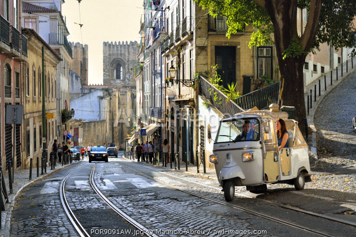 A tuk tuk in Alfama district with the Motherchurch (Se Catedral) in the background. Lisbon, Portugal